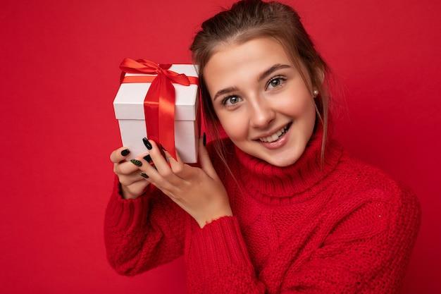 Mooie gelukkige jonge donkerbruine vrouw die over kleurrijke muurmuur wordt geïsoleerd die modieuze vrijetijdskleding draagt die giftdoos houdt en.