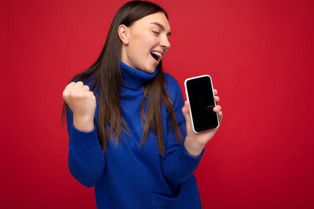 Mooie gelukkige jonge donkerbruine vrouw die toevallige blauwe geïsoleerde sweater draagt