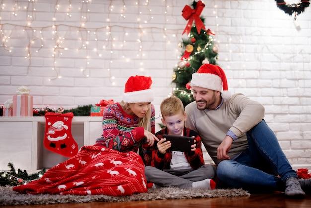 Mooie gelukkige jonge familie genieten van kerstvakantie thuis zittend op een tapijt en kijken naar een tablet.