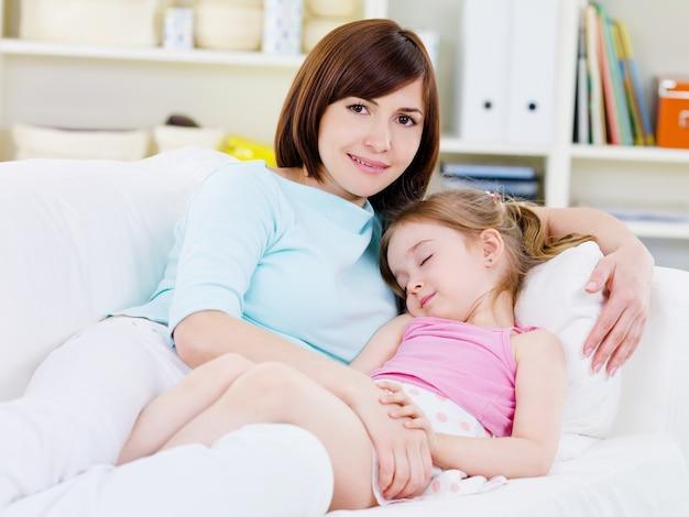 Mooie gelukkige jonge moeder met kleine slapende dochter op een bank thuis