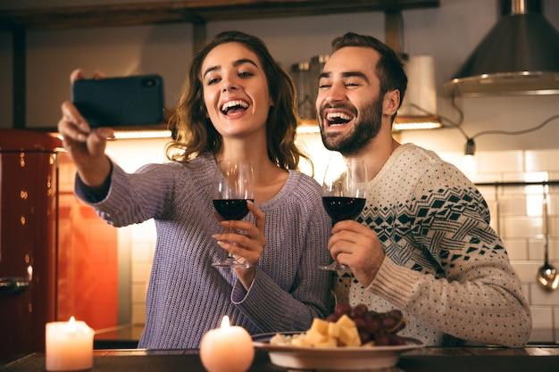 Mooie gelukkige jonge paar romantische avond samen thuis doorbrengen, rode wijn drinken, een selfie nemen