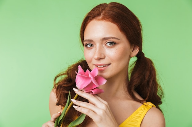 Mooie gelukkige jonge roodharige meisje poseren geïsoleerd over groene muur achtergrond met bloem.