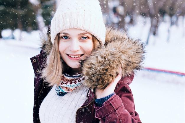 Mooie gelukkige jonge vrouw die de handschoenen van de winterhoed draagt die met sneeuwvlokken worden behandeld
