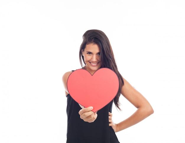 Mooie gelukkige jonge vrouw die een groot rood hart voor valentijnsdag houdt