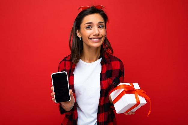 Mooie gelukkige jonge vrouw die over rode muur wordt geïsoleerd als achtergrond die witte toevallige t-shirt draagt