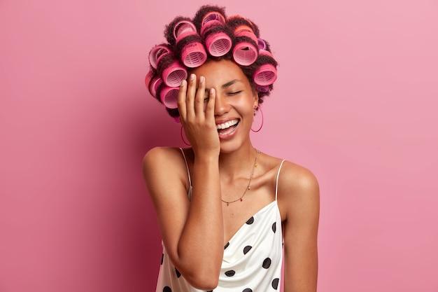 Mooie gelukkige jonge vrouw doet kapsel met haarrollers, maakt gezicht handpalm en kan niet stoppen met lachen, hoort iets heel grappigs, nonchalant gekleed, brengt vrije tijd thuis door. haar zorg concept
