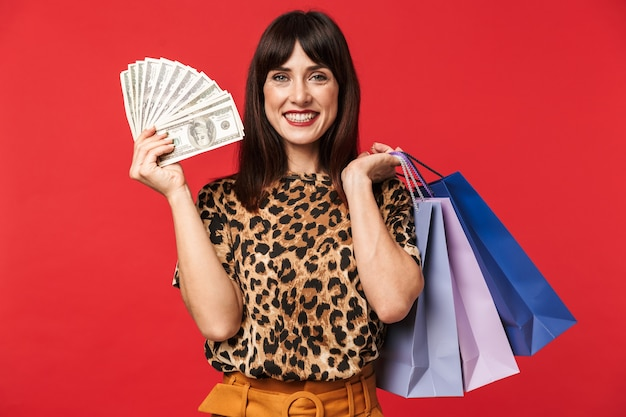 Mooie gelukkige jonge vrouw gekleed in dier gedrukt shirt poseren geïsoleerd over rode muur met geld en boodschappentassen.