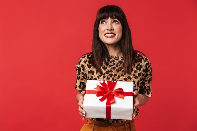 Mooie gelukkige jonge vrouw gekleed in een dier bedrukt shirt poseren geïsoleerd over rode muur met huidige doos.