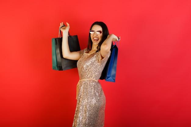 Mooie gelukkige jonge vrouw glimlachend en boodschappentassen te houden