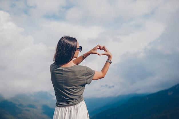 Mooie gelukkige jonge vrouw in bergen op de achtergrond van mist
