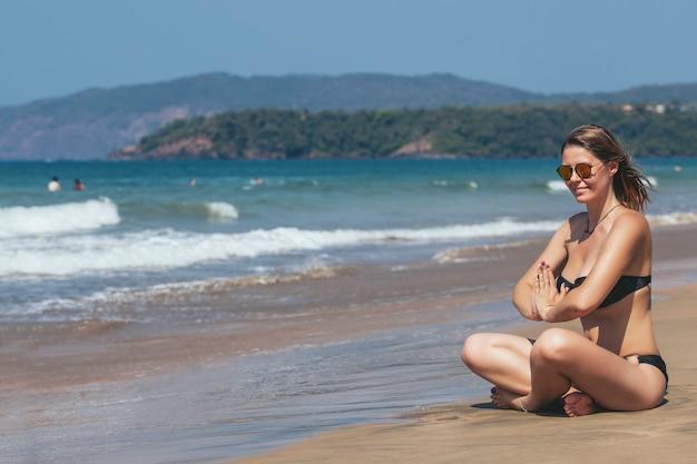 Mooie gelukkige jonge vrouw in bikini op zandig oceaanstrand