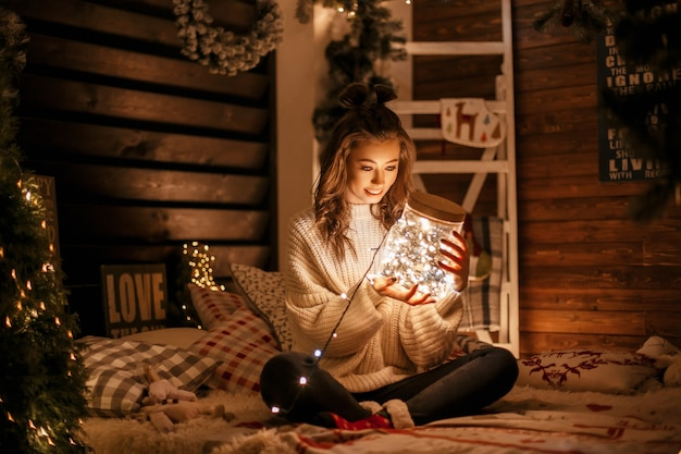Mooie gelukkige jonge vrouw in een gebreide vintage trui met een magische pot met feestelijke lampjes op het bed