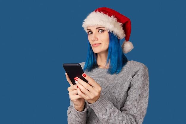 Mooie gelukkige jonge vrouw in kerstmuts met smartphone over blauwe achtergrond