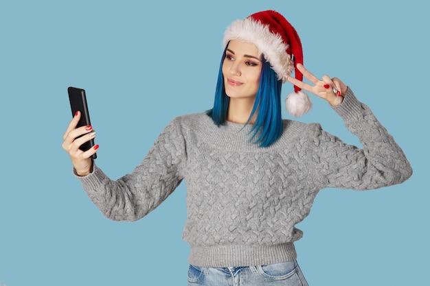 Mooie gelukkige jonge vrouw in kerstmuts neemt selfie over blauwe achtergrond blue