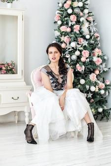 Mooie gelukkige jonge vrouw in mooie jurk met make-up en kapsel in kerstversiering