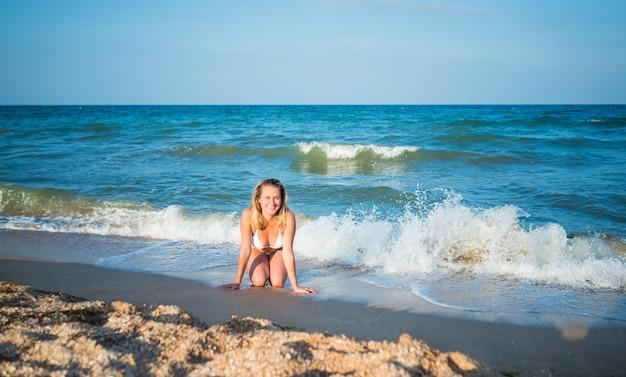 Mooie gelukkige jonge vrouw ligt op het natte zand naast de opspattende golven op hete zomerdag tijdens vakantie.