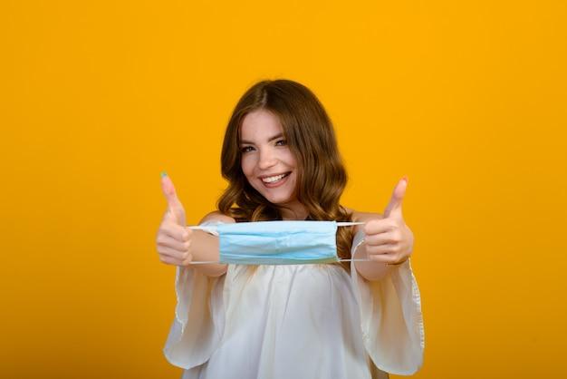 Mooie gelukkige jonge vrouw met gezichtsmasker in handen. covid-virus en luchtverontreiniging. herstellen van ziekte, einde van epidemie.
