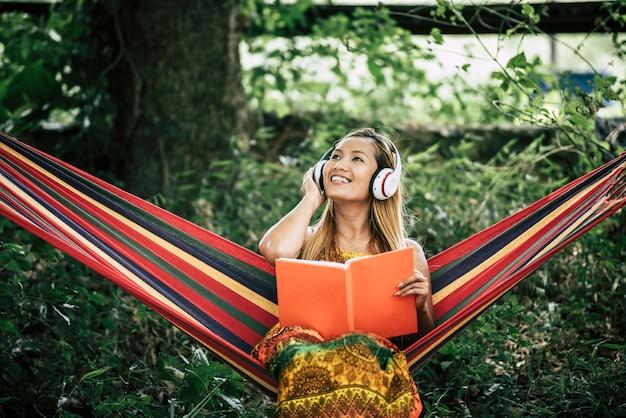 Mooie gelukkige jonge vrouw met hoofdtelefoons die aan muziek luisteren en een boek lezen