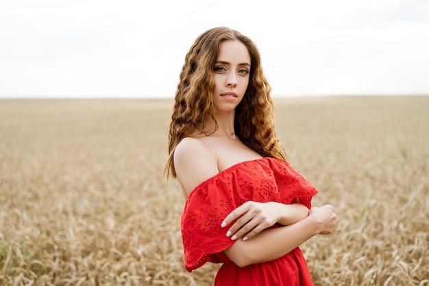 Mooie gelukkige jonge vrouw met krullend haar in een rode jurk poseren in een tarweveld