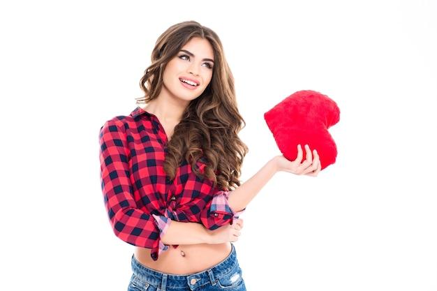 Mooie gelukkige jonge vrouw met lang krullend haar die rood hart in de hand houdt die zich over witte muur bevindt