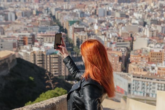 Mooie gelukkige jonge vrouw neemt zelfportret met haar telefoon in de stad