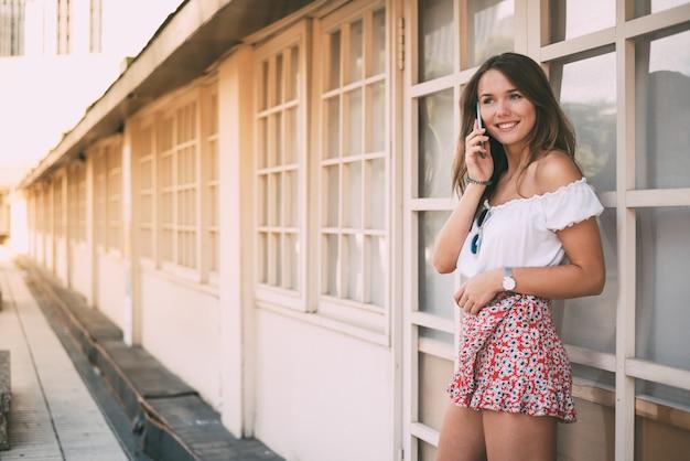 Mooie gelukkige jonge vrouw op de mobiele telefoon
