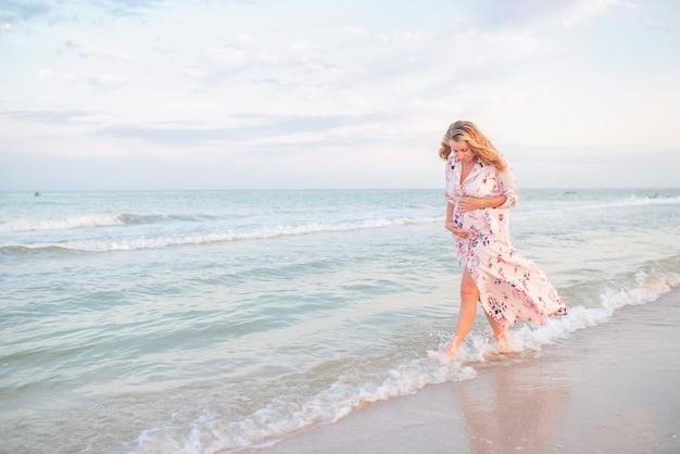 Mooie gelukkige jonge zwangere vrouw in een lichte zomerkleding die haar buik koestert