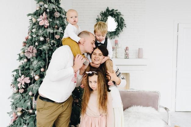 Mooie gelukkige kaukasische familie van vijf dichtbij de kerstboom