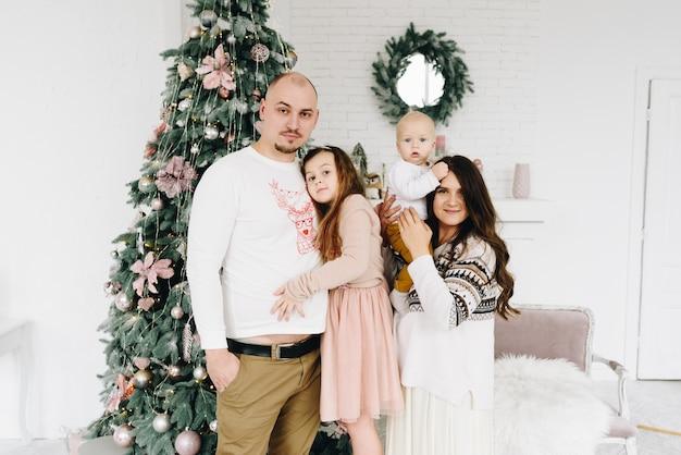 Mooie gelukkige kaukasische gezin van vier in de buurt van de kerstboom