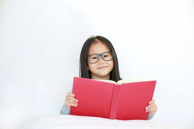 Mooie gelukkige kleine aziatische jongen meisje hardcover boek lezen liggend op bed tegen een witte achtergrond.