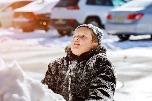 Mooie gelukkige kleine jongen spelen met sneeuw in een sneeuw op de oprit naar huis