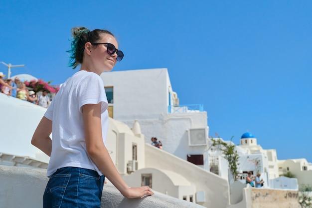 Mooie gelukkige meisjestoerist op het eiland santorini in griekenland, vrouwelijke tiener die door de middellandse zee reist witte beroemde eilandarchitectuur en blauwe hemelachtergrond, kopieer ruimte