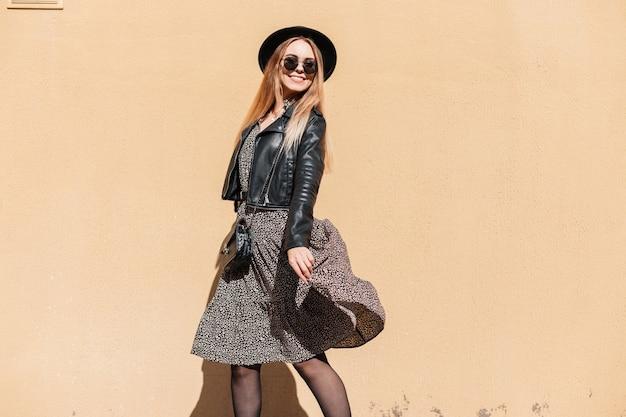 Mooie gelukkige modelvrouw met een schattige glimlach in zonnebril en een hoed in een leren jas met een jurk en een kleine handtas danst in de buurt van een geelbeige muur