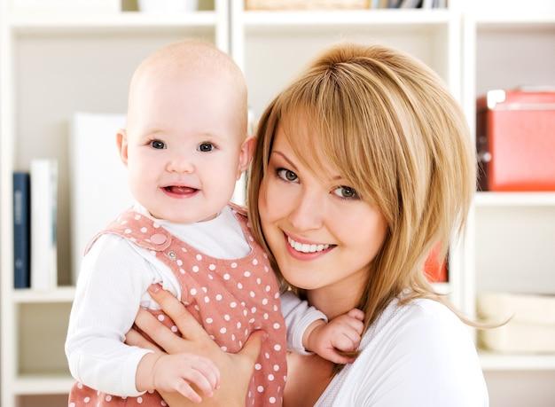 Mooie gelukkige moeder die pasgeboren baby op handen houdt - binnenshuis