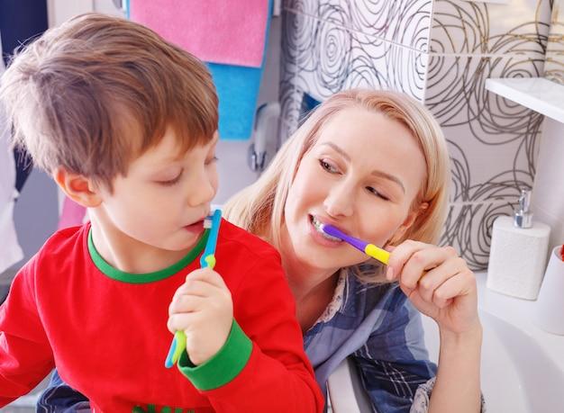 Mooie gelukkige moeder en zoontje in bathrom tandenpoetsen samen