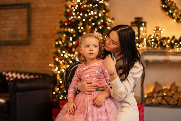 Mooie gelukkige moeder vrouw met dochtertje in modieuze kleding zit op de achtergrond van een kerstboom, versieringen en verlichting