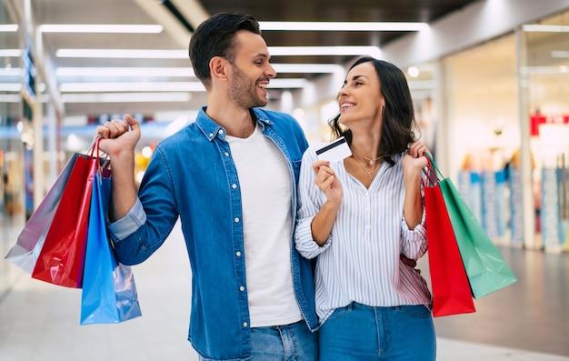 Mooie gelukkige opgewonden paar verliefd of familie met papieren zakken en creditcard in handen tijdens het wandelen tijdens het winkelen in het winkelcentrum