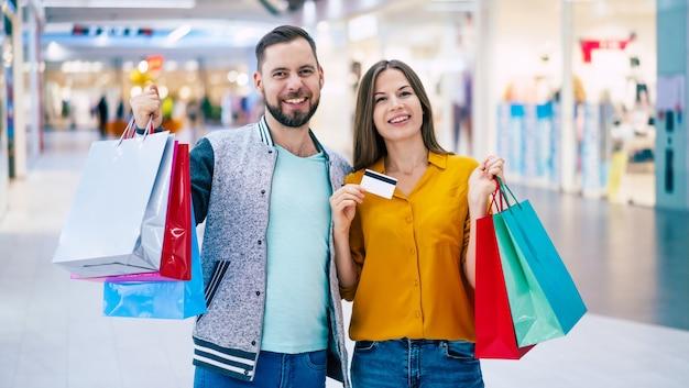 Mooie gelukkige opgewonden verliefde paar of familie met papieren zakken in handen tijdens het wandelen tijdens het winkelen in het winkelcentrum