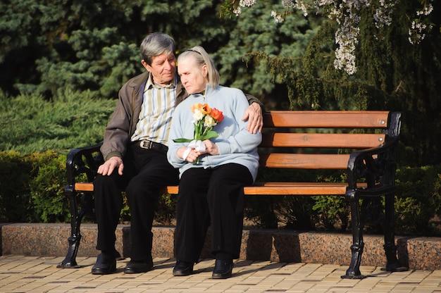 Mooie gelukkige oude mensen die in het de herfstpark zitten