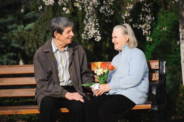 Mooie gelukkige oude mensen zitten in het voorjaar park