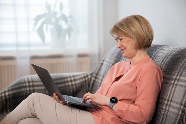 Mooie gelukkige oudere gepensioneerde senior vrouw freelancer gebruikt, werkt op laptop zittend op de bank