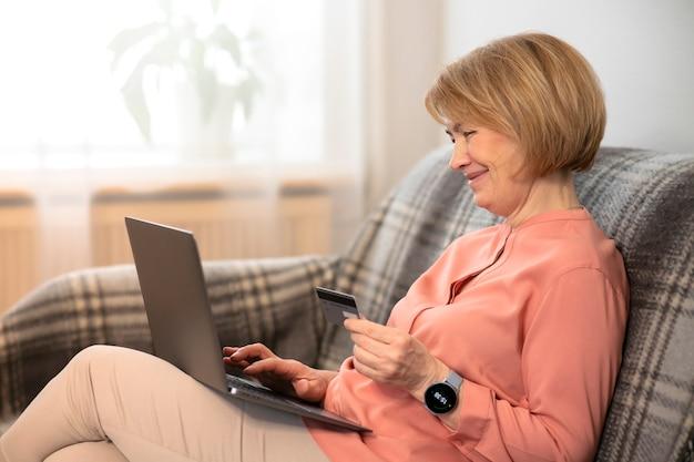 Mooie gelukkige oudere senior vrouw zittend op de bank thuis met laptop, online kopen met creditcard