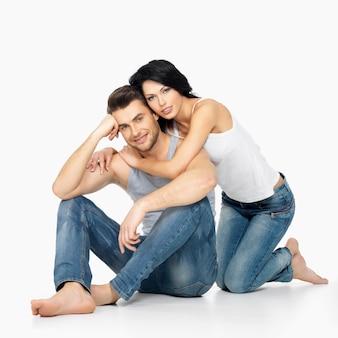 Mooie gelukkige paar verliefd op wit gekleed in blauwe jeanse en wit onderhemd