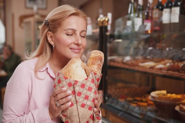 Mooie gelukkige rijpe vrouw die geniet van geur van heerlijk vers gebakken brood, exemplaarruimte