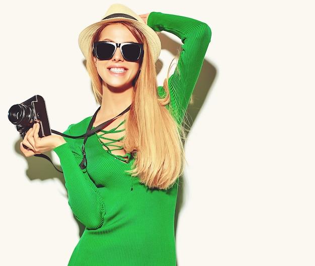 Mooie gelukkige schattige blonde vrouw meisje in casual zomer groene hipster kleding maakt foto's met retro fotografische camera