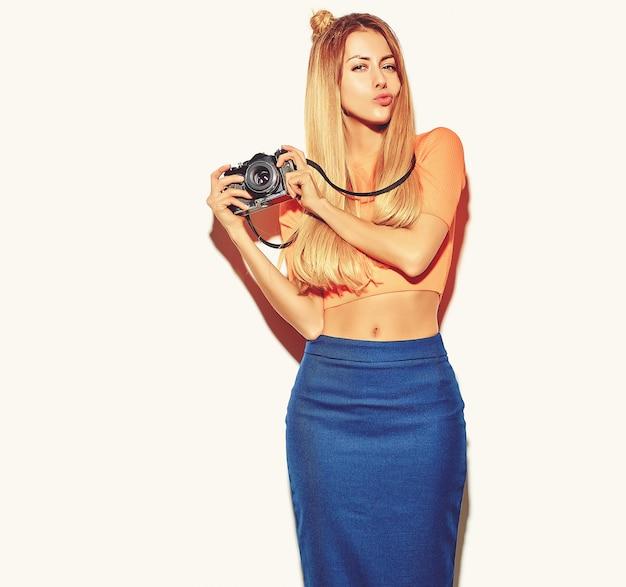 Mooie gelukkige schattige blonde vrouw meisje in casual zomer hipster kleding neemt foto's met retro fotografische camera geïsoleerd op een witte en het maken van een eend gezicht