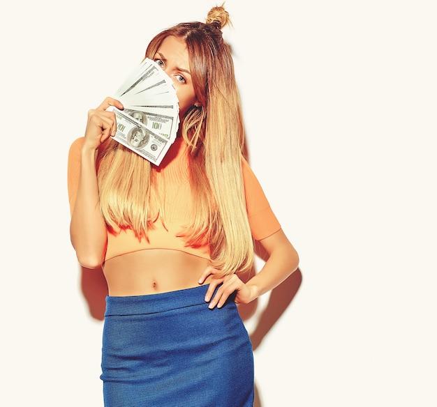 Mooie gelukkige schattige lachende blonde vrouw meisje in casual kleurrijke hipster zomer kleding zonder make-up houden dollar bankbiljetten