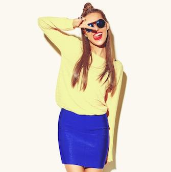 Mooie gelukkige schattige lachende brunette vrouw meisje in casual kleurrijke hipster gele zomer kleding met rode lippen op wit wordt geïsoleerd met vredesteken en haar tong