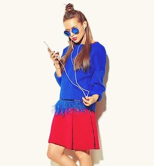 Mooie gelukkige schattige lachende sexy brunette vrouw meisje in casual kleurrijke zomer kleding met rode lippen geïsoleerd op wit luisteren naar muziek en een koptelefoon te houden