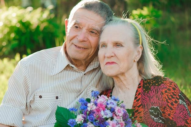 Mooie gelukkige tachtig jaar oude mensen die in het park zitten